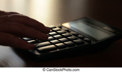 Silhouette of female hand typing numbers on the keypad...