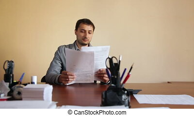 Man employee in the office scatters documents upset tired