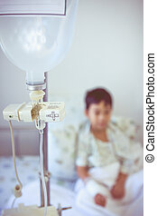 Asian boy sitting on sickbed with infusion pump intravenous...