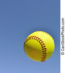 Yellow Softball in the Air Against a Blue Sky