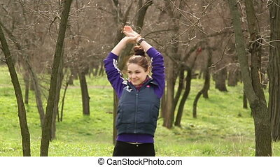 Girl doing stretching warming up before exercise in the...