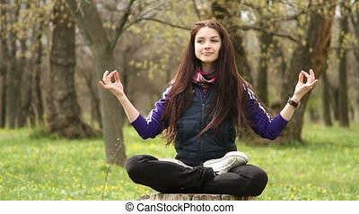 Forest, girl sitting on a stump in the lotus position  Yoga