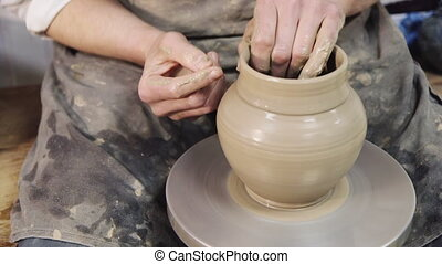 The potter makes a pot of wet clay, handmade crafts