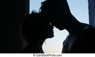 man and woman kissing near a window. silhouette