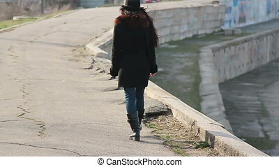 Beautiful girl with glasses and hat walks along the concrete...