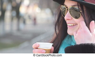 Beautiful girl in glasses and a hat on the street drinking...