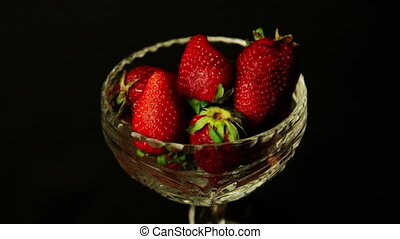 strawberries in a bowl on dark background