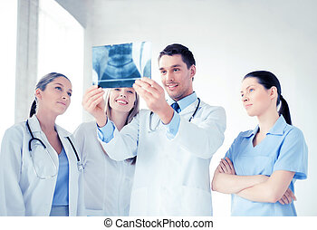 young group of doctors looking at x-ray - picture of young...
