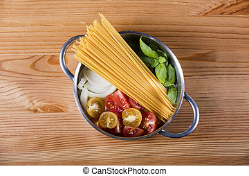 Raw pasta, tomato, basil and onion in pot on wooden background