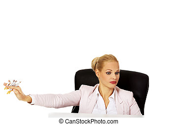 Business woman sitting behind the desk dont want to smoke