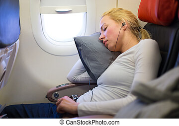 Lady traveling napping on a plain. - Tired blonde casual...
