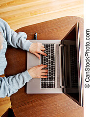 Senior sitting at table and using laptop