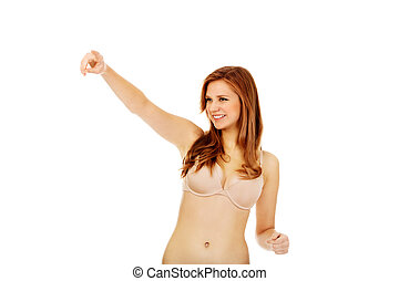 Woman in beige underwear pointing for something