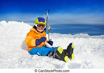 Boy sit in snow with ski mask and helmet - Little boy with...