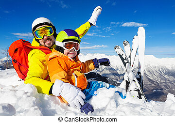 Dad and son skiers sit in snow on mountain top - Little boy...