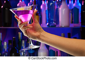 Alcohol drink glass in woman hand inside bar