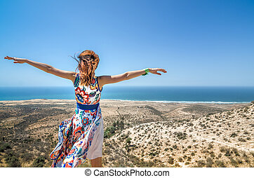 Beautiful happy young woman spread arms looking to the ocean