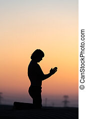 Praying man silhouette sitting alone in desert at sunset