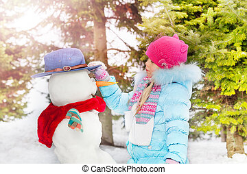 Little girl with make snowball in the winter park
