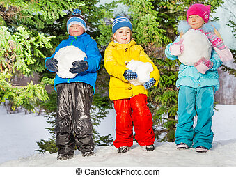 Little kids with big snowballs in the park