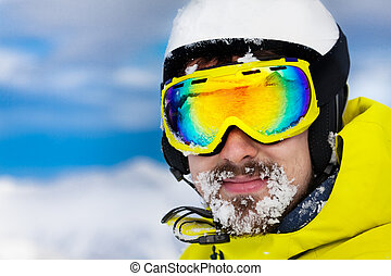 Skier man with snow on beard wear helmet and mask - Close...