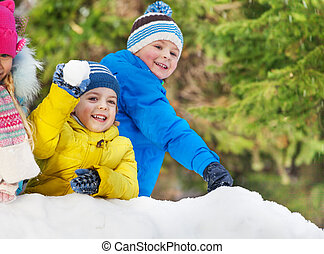 Little boys throw snowballs in the winter park