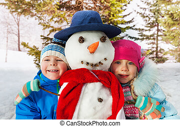 Boy and girl together with dressed snowman