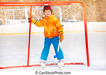Little boy standing with hockey stick smiling