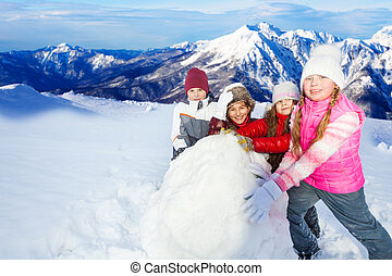 Four friends rolling the huge snowball on hill - Four...