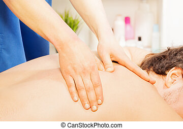 Man enjoying a deep tissue back massage - Man lying in a spa...