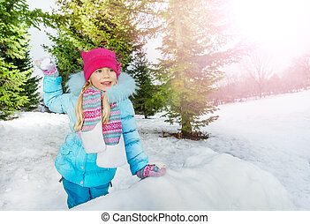 Little girl throw snowball in park - Little girl behind the...