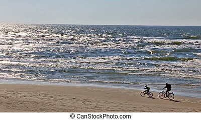 Sport Activities family riding a bicycle on sea shore