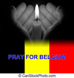 hands holding a burning candle in dark like a heart in grey tone with pray for Belgium on bottom