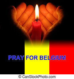 hands holding a burning candle in dark like a heart with pray for Belgium on bottom