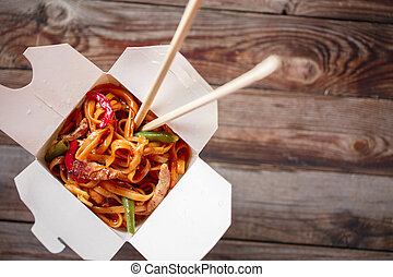 Noodles with pork and vegetables in take-out box on wooden...