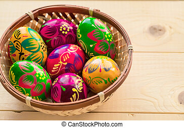 Beautiful painted colorful Easter eggs in a wickerwork nest on a light wooden background