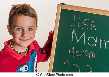 schoolboy with school board - one child writes the word mom...
