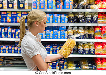 woman shopping in a supermarket - a young woman shopping...