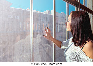 Pretty sexy woman looking at bright dirty window
