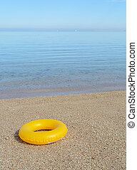 yellow inflatable paddling circle in the sand near the sea