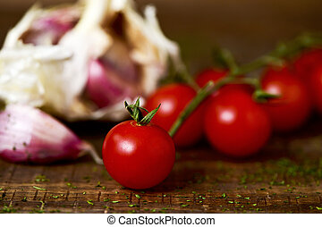 cherry tomatoes and garlics on a wooden table - closeup of...