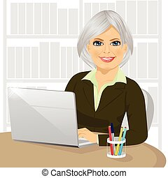 successful mature businesswoman working typing on her laptop at office