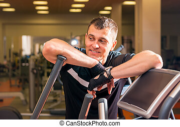 handsome adult man in the gym resting near simulator