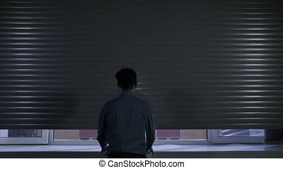 Man opening and sliding blinds on the office window