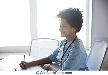 happy female doctor or nurse writing at hospital