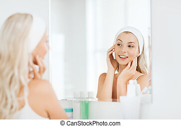 woman in hairband touching her face at bathroom - beauty,...