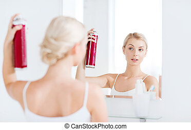woman with hairspray styling her hair at bathroom - beauty,...