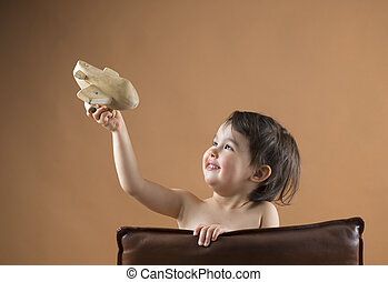 Happy kid playing with toy airplane. Studio shot
