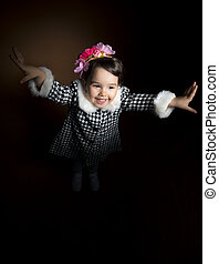 Happy beautiful little girl screaming with her hands up on black background, studio shot. Little girl playing