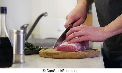Cutting meat on a wooden kitchen board in day